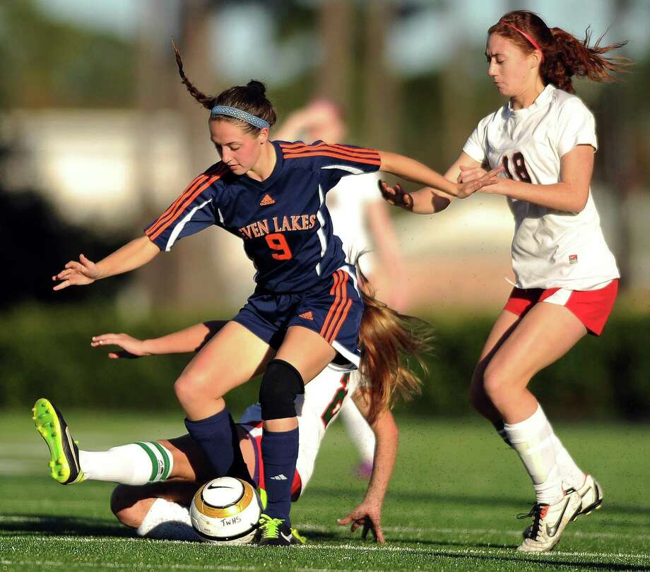 Seven Lakes' Katy Byrne (9) avoids the tackle of The Woodlands' Kelly Barbalias as teammate Carissa Cannizzaro defends during the second half of a high school soccer game, Saturday, January 11, 2014, at Moorhead Stadium in Conroe. Photo: Eric Christian Smith, For The Chronicle