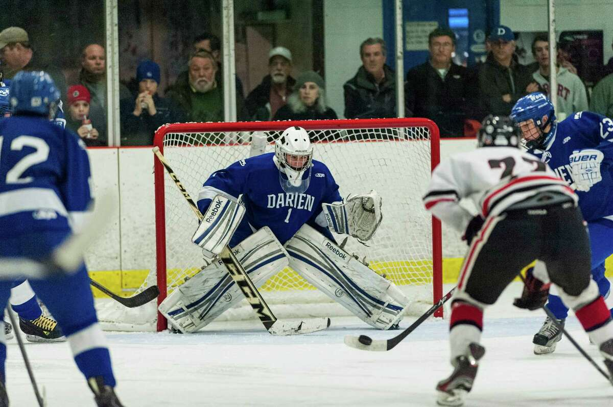 Darien high school goalie Michael Colon keeps his eyes on the puck as teammate Carter Joyce tries to clear it out from in front of the goal during a boys ice hockey game against New Canaan high school played at Darien Ice Rink, Darien CT on Saturday, January, 11th, 2014.