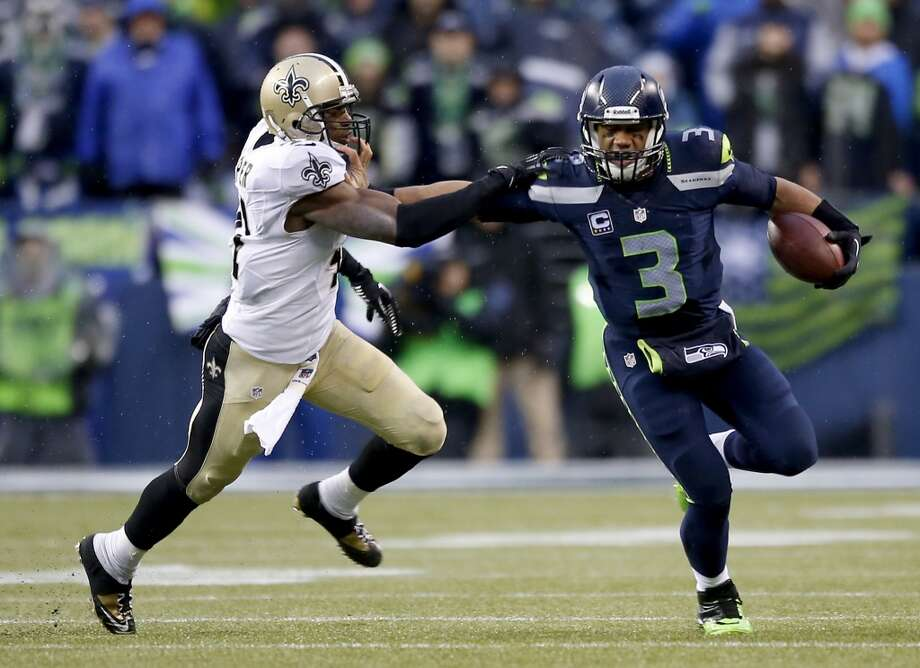 Quarterback Russell Wilson #3 of the Seahawks pushes back strong safety Roman Harper #41 of the Saints. Photo: Otto Greule Jr, Getty Images