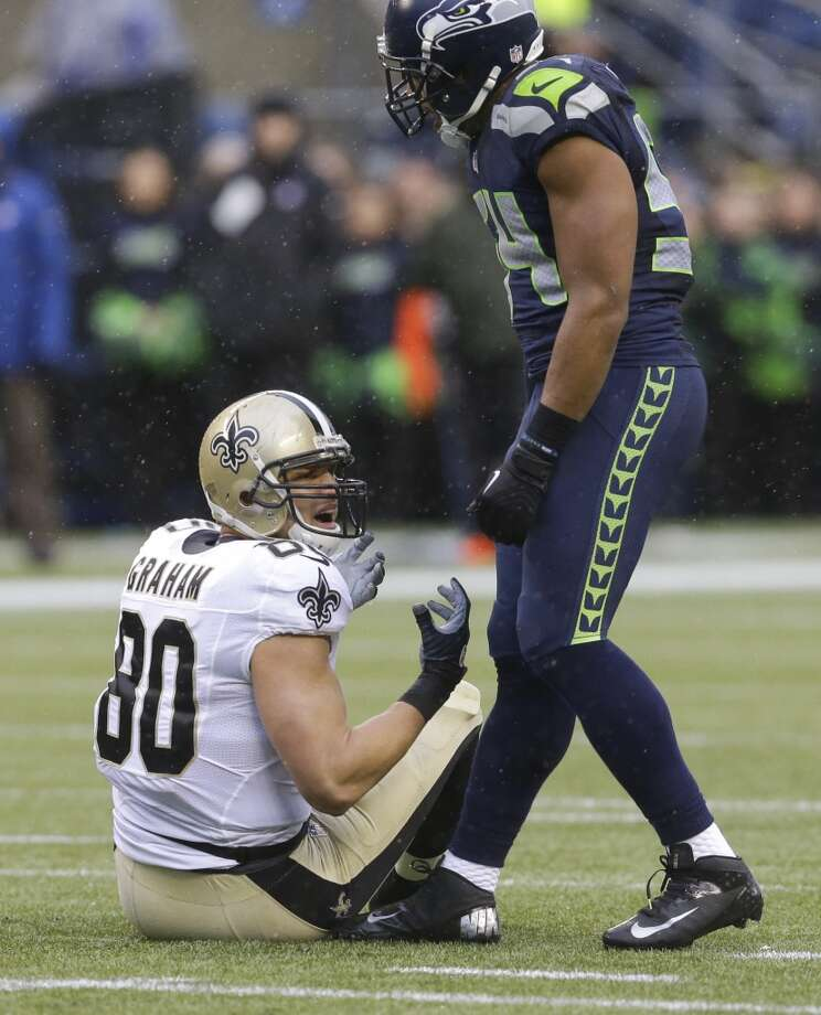 Saints tight end Jimmy Graham, left, sits on the ground next to Seahawks middle linebacker Bobby Wagner. Photo: Ted S. Warren, Associated Press
