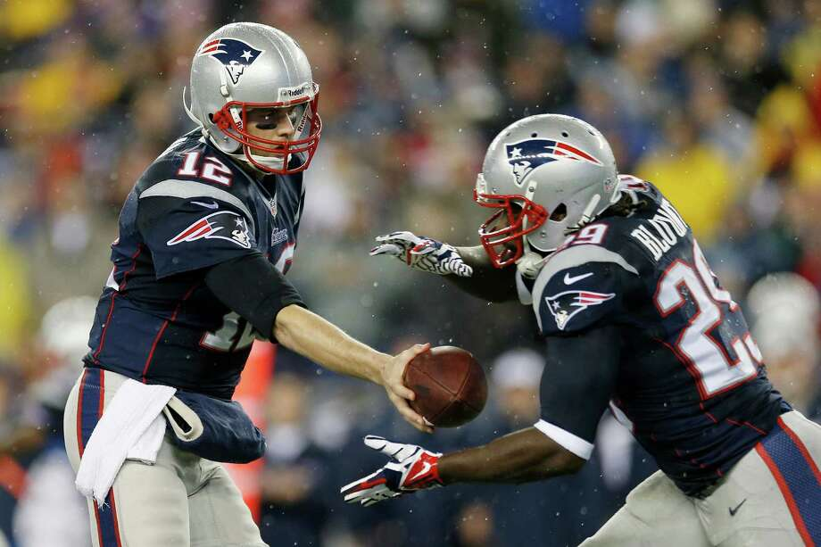 New England Patriots quarterback Tom Brady (12) hands off the ball to running back LeGarrette Blount (29) during the first half of an AFC divisional NFL playoff football game against the Indianapolis Colts in Foxborough, Mass., Saturday, Jan. 11, 2014. Photo: Michael Dwyer, AP / AP