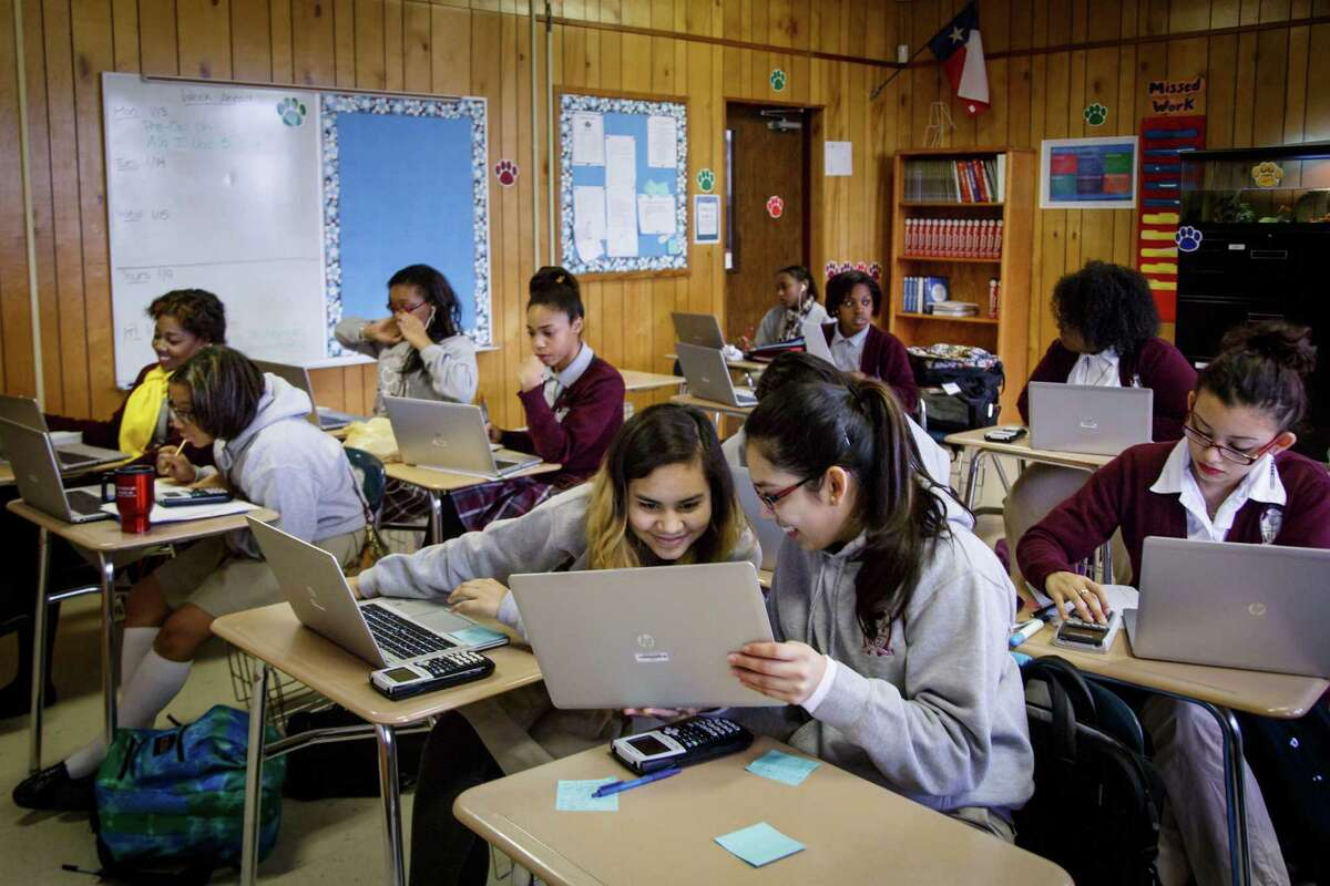 Jackie Cornejo, 16, left, and Elisa Martinez, 16, work together on a problem during their pre-calculus class at the Young Women's College Preparatory Academy. The academy is one of HISD's first schools to get laptops.