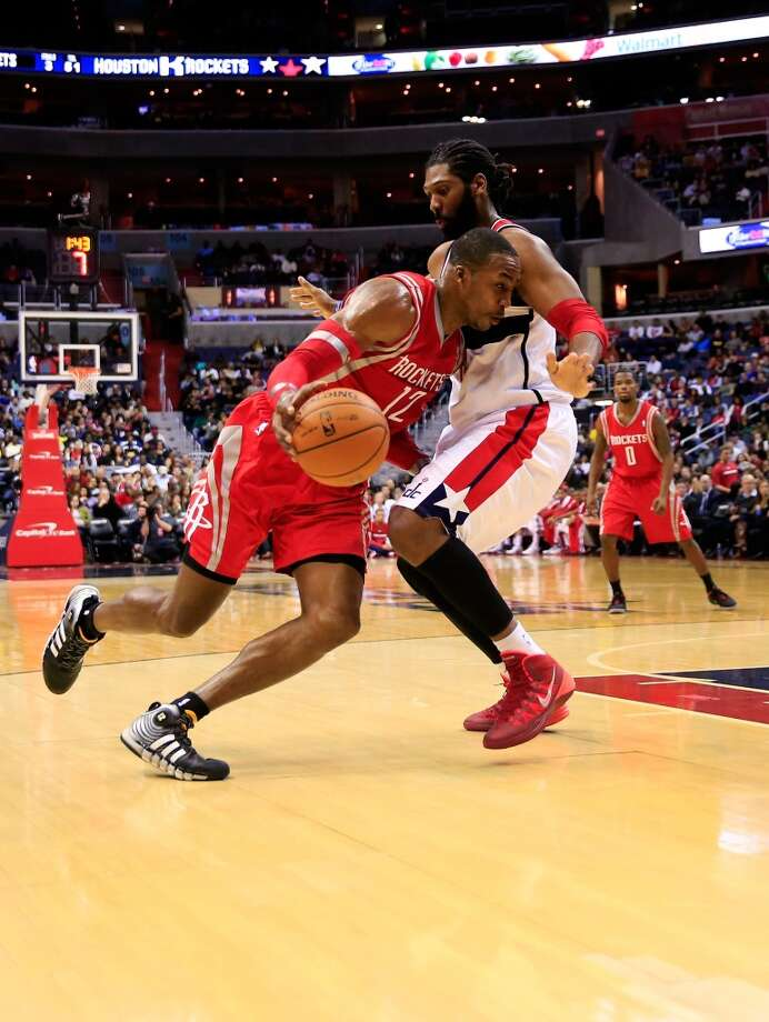 Dwight Howard #12 drives around Nene Hilario #42. Photo: Rob Carr, Getty Images