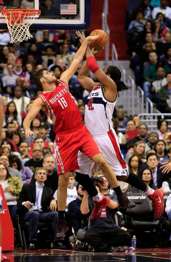 Omri Casspi blocks a shot by Nene Hilario. Photo: Rob Carr, Getty Images