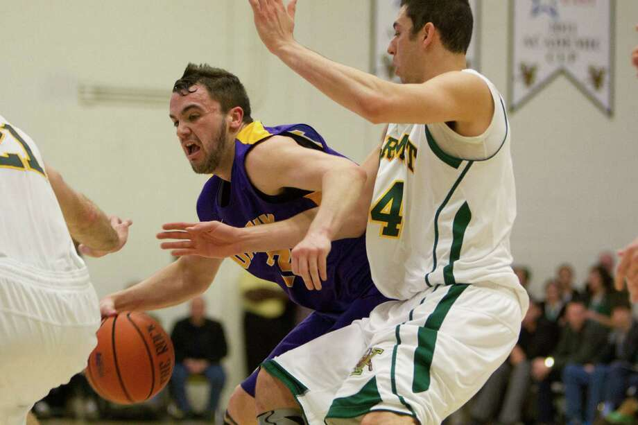 Peter Hooley (left) of UAlbany is fouled on his way to the hoop by Vermont's Josh Elbaum (14) during the Great Danes defeat against the Catamounts at Patrick Gymnasium in Burlington, VT on January 11, 2014 (Shane Bufano/For The Times Union) Photo: Shane Bufano / Copyright: Shane Bufano Photography