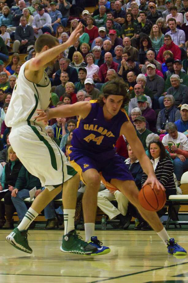 John Puk (right) of UAlbany drives the lane as he is defended by Vermont's Ethan O'Day (left) during the Great Danes 68-38 defeat against the Catamounts at Patrick Gymnasium in Burlington, VT on January 11, 2014 (Shane Bufano/For The Times Union) Photo: Shane Bufano / Copyright: Shane Bufano Photography
