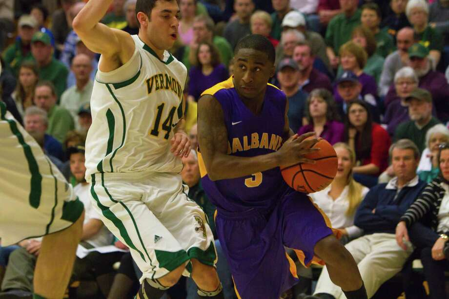 DJ Evans (right) of UAlbany drives the lane as he is defended by Vermont's Josh Elbaum (left) during the Great Danes defeat against the Catamounts at Patrick Gymnasium in Burlington, VT on January 11, 2014 (Shane Bufano/For The Times Union) Photo: Shane Bufano / Copyright: Shane Bufano Photography