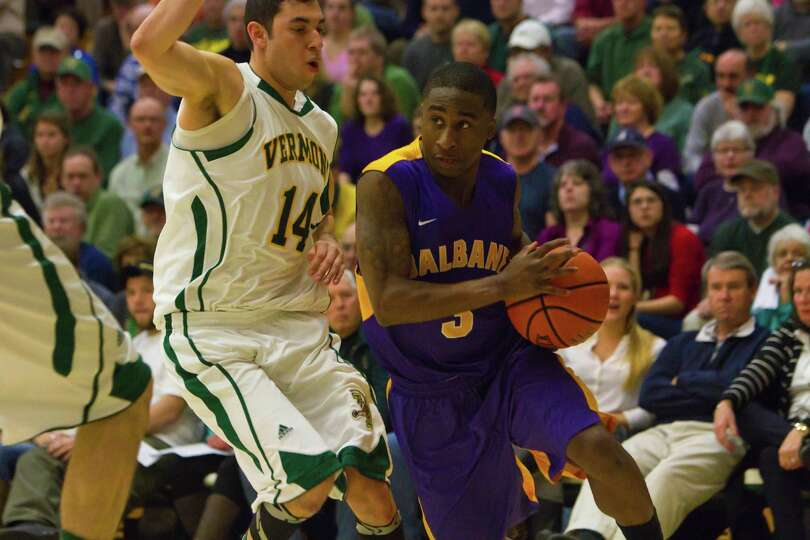 DJ Evans (right) of UAlbany drives the lane as he is defended by Vermont's Josh Elbaum (left) during