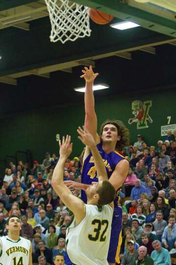 John Puk (44) of UAlbany scores a basket for the Great Danes over Vermont's Ethan O'Day.  The Great