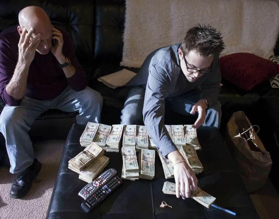 Ryan Kunkel (right), a co-owner of five marijuana dispensaries, counts tens of thousands of dollars cash beside his business partner, Joel Berman, at his office in Seattle. Legal marijuana businesses are being conducted mostly in cash because banks across the country have been reluctant to provide accounts and other services to them. Photo: David Ryder / New York Times / NYTNS