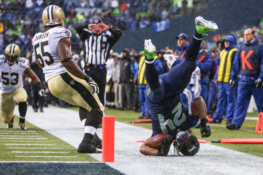 Seattle Seahawks player Marshawn Lynch goes upside down as he tries to keep a ball inbounds againt the New Orleans Saints during the NFC Divisional Playoff game on Saturday, January 11, 2014 at CenturyLink Field in Seattle. Photo: JOSHUA TRUJILLO, SEATTLEPI.COM