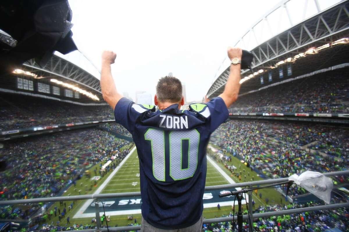 Former Seattle Seahawks quarterback Jim Zorn throws up his arms after raising the 12th Man flag during the NFC Divisional Playof game against the New Orleans Saints on Saturday, January 11, 2014 at CenturyLink Field in Seattle.