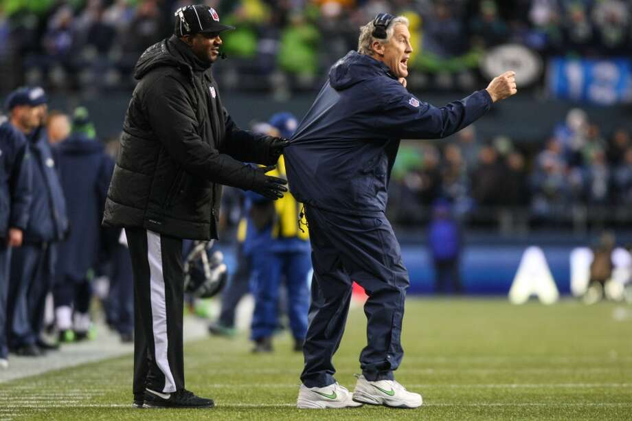An official restrains Seattle Seahawks coach Pete Carroll as he disputes a call during play against the New Orleans Saints in second half of an NFC Divisional Playoff game on Saturday, January 11, 2014 at CenturyLink Field in Seattle. Photo: JOSHUA TRUJILLO, SEATTLEPI.COM