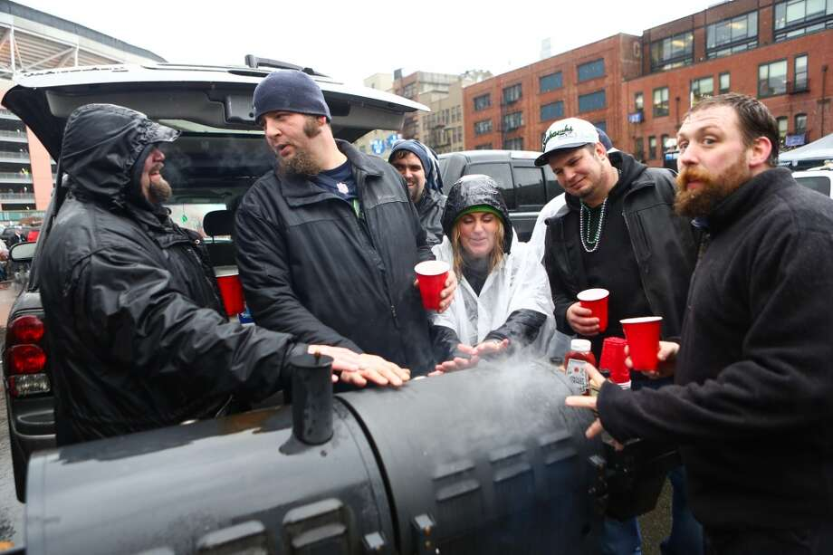 Fans warm their hans on a grill as they tailgate during the NFC Divisional Playoff game between the New Orleans Saints and Seattle Seahawks on Saturday, January 11, 2014 at CenturyLink Field in Seattle. Photo: JOSHUA TRUJILLO, SEATTLEPI.COM