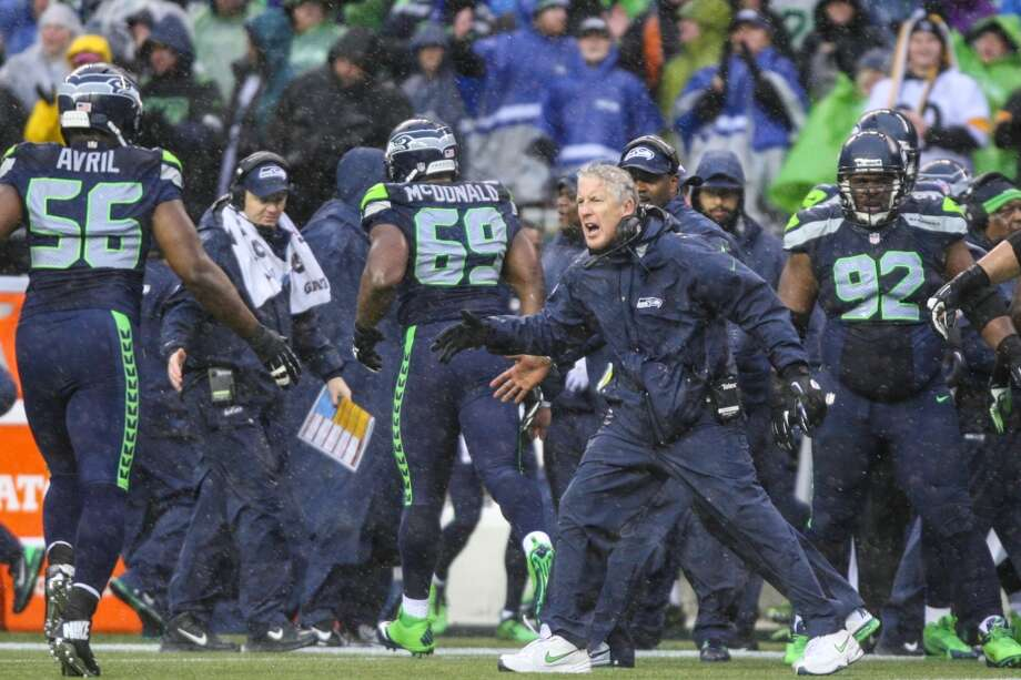 Seattle Seahawks coach Pete Carroll greets Cliff Avril after a play in howling wind and rain against the New Orleans Saints on Saturday, January 11, 2014 at CenturyLink Field in Seattle. Photo: JOSHUA TRUJILLO, SEATTLEPI.COM