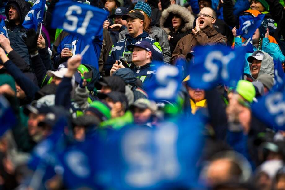 "Fans hoist ""12th Man"" flags during the first half of a playoff game Saturday, Jan. 11, 2014, at CenturyLink Field in Seattle. The Seahawks led the Saints 16-0 at the half. Photo: JORDAN STEAD, SEATTLEPI.COM"