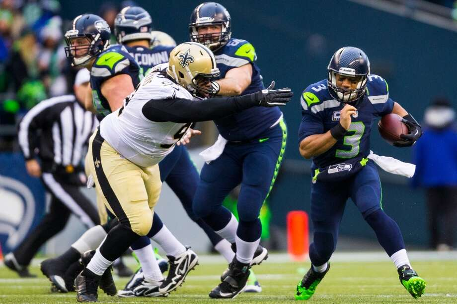 Seahawks quarterback Russell Wilson, right, charges through a hole in New Orleans' defense during the first half of a playoff game Saturday, Jan. 11, 2014, at CenturyLink Field in Seattle. The Seahawks led the Saints 16-0 at the half. Photo: JORDAN STEAD, SEATTLEPI.COM