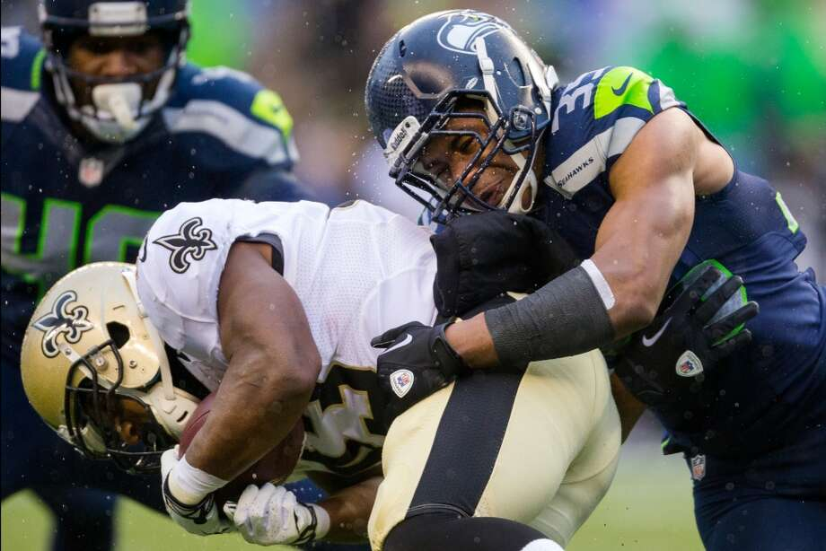 Seahawk DeShawn Shead, right, tackles a ball-carrying Saints player during the first half of a playoff game Saturday, Jan. 11, 2014, at CenturyLink Field in Seattle. The Seahawks led the Saints 16-0 at the half. Photo: JORDAN STEAD, SEATTLEPI.COM