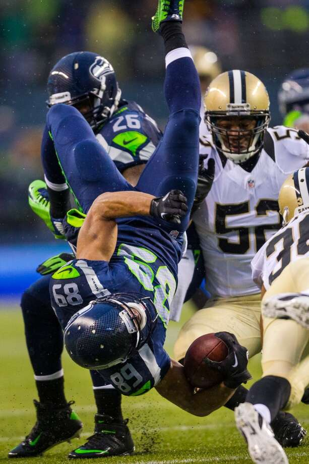 Seahawk Doug Baldwin, center, is knocked head over heels while on his way downfield during the second half of a playoff game against the New Orleans Saints Saturday, Jan. 11, 2014, at CenturyLink Field in Seattle. The Seahawks beat the Saints 23-15 and will advance to the second game of the playoffs. Photo: JORDAN STEAD, SEATTLEPI.COM