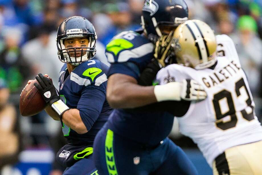 Seahawks quarterback Russell Wilson, left, looks for a pass despite New Orleans' defense during the first half of a playoff game Saturday, Jan. 11, 2014, at CenturyLink Field in Seattle. The Seahawks led the Saints 16-0 at the half. Photo: JORDAN STEAD, SEATTLEPI.COM