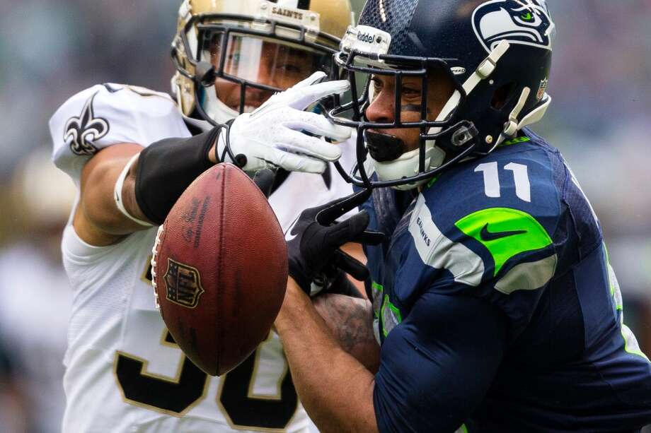 Seahawk Percy Harvin, right, loses his grip on a pass from Russell Wilson during the first half of a playoff game Saturday, Jan. 11, 2014, at CenturyLink Field in Seattle. The Seahawks led the Saints 16-0 at the half. Photo: JORDAN STEAD, SEATTLEPI.COM