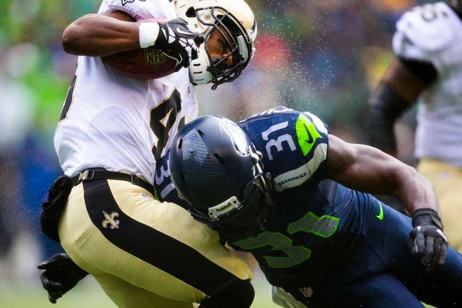 With a spray of icy rain, Seahawk Kam Chancellor, right, collides with a New Orleans Saints player during the first half of a playoff game Saturday, Jan. 11, 2014, at CenturyLink Field in Seattle. The Seahawks led the Saints 16-0 at the half. Photo: JORDAN STEAD, SEATTLEPI.COM