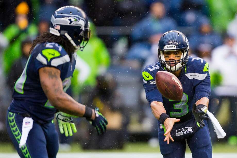Seahawks quarterback Russell Wilson, right, pitches the ball to running back Marshawn Lynch, left, during a playoff game against the New Orleans Saints Saturday, Jan. 11, 2014, at CenturyLink Field in Seattle. The Seahawks led the Saints 16-0 at the half. Photo: JORDAN STEAD, SEATTLEPI.COM
