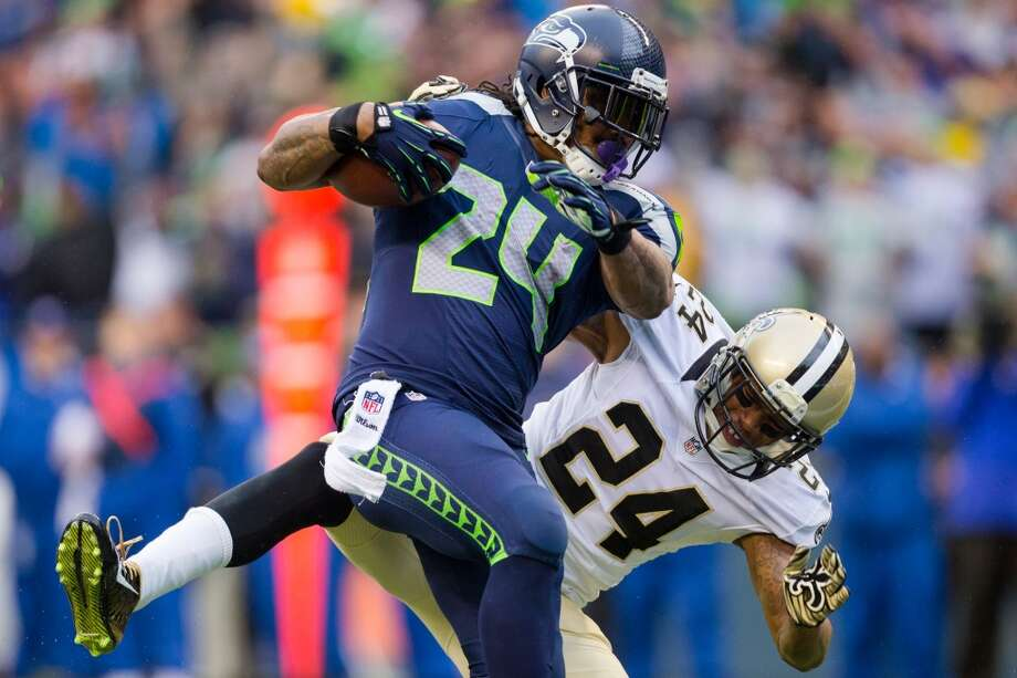 Seahawks running back Marshawn Lynch, left, tumbles toward the end zone for his first touchdown of a playoff game against the New Orleans Saints Saturday, Jan. 11, 2014, at CenturyLink Field in Seattle. The Seahawks led the Saints 16-0 at the half. Photo: JORDAN STEAD, SEATTLEPI.COM