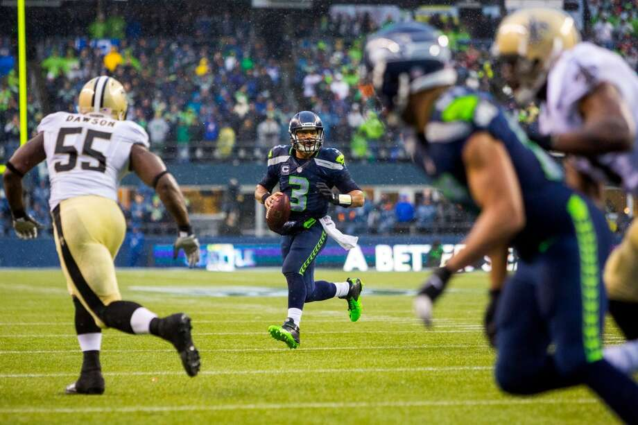 Seahawks quarterback Russell Wilson searches for a teammate to pass to during the first half of a playoff game Saturday, Jan. 11, 2014, at CenturyLink Field in Seattle. The Seahawks led the Saints 16-0 at the half. Photo: JORDAN STEAD, SEATTLEPI.COM
