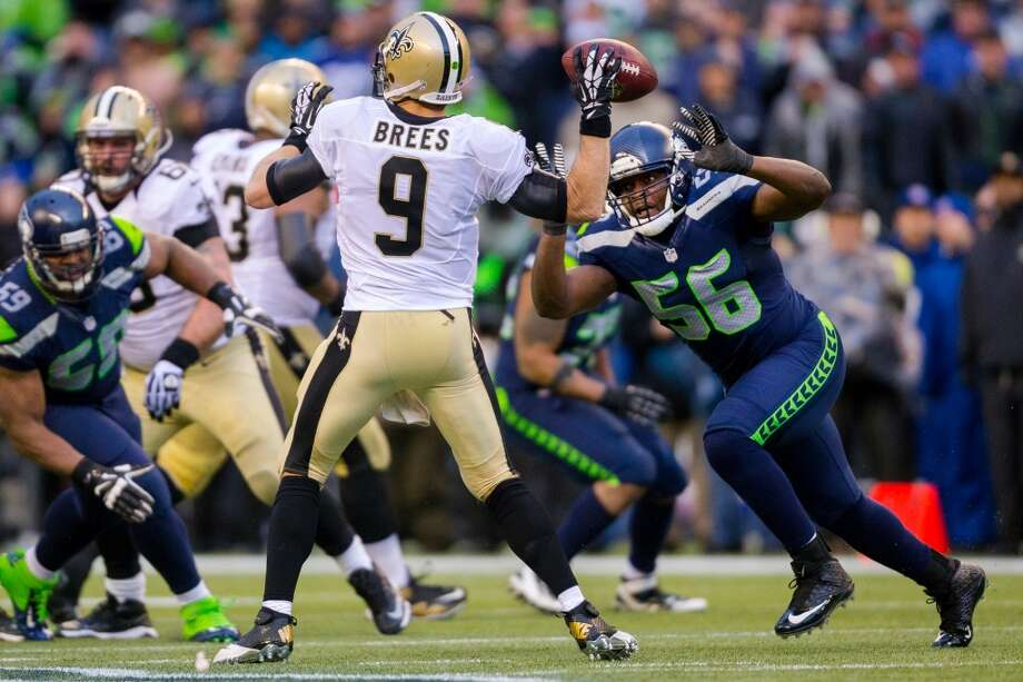 Seahawk Cliff Avril, right, runs to attempt a sack on Saints' quarterback Drew Brees, center, during the second half of a playoff game Saturday, Jan. 11, 2014, at CenturyLink Field in Seattle. The Seahawks beat the Saints 23-15 and will advance to the second game of the playoffs. Photo: JORDAN STEAD, SEATTLEPI.COM