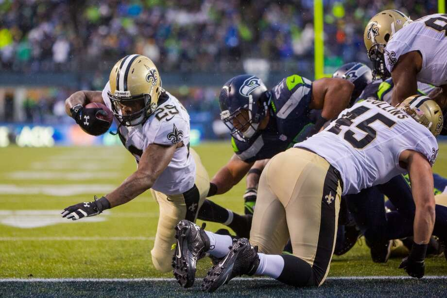 Saints running back Khiry Robinson, left, dives into the end zone for a touchdown during the second half of a playoff game Saturday, Jan. 11, 2014, at CenturyLink Field in Seattle. The Seahawks beat the Saints 23-15 and will advance to the second game of the playoffs. Photo: JORDAN STEAD, SEATTLEPI.COM