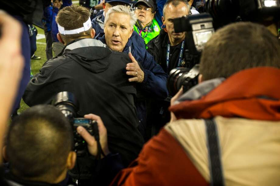 Seahawks head coach Pete Carroll, top left, hugs New Orleans Saints head coach Sean Payton following a playoff game Saturday, Jan. 11, 2014, at CenturyLink Field in Seattle. The Seahawks beat the Saints 23-15 and will advance to the second game of the playoffs. Photo: JORDAN STEAD, SEATTLEPI.COM
