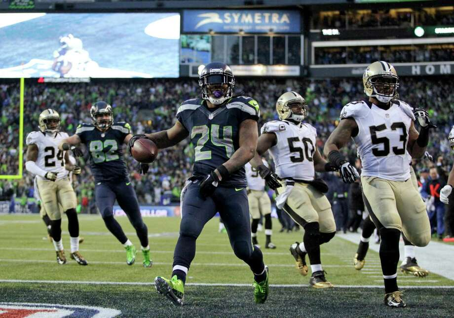Seattle Seahawks running back Marshawn Lynch (24) arrives in the end zone with a 31-yard touchdown during the fourth quarter of an NFC divisional playoff NFL football game against the New Orleans Saints in Seattle, Saturday, Jan. 11, 2014. (AP Photo/John Froschauer) ORG XMIT: SEA152 Photo: John Froschauer / FR74207 AP