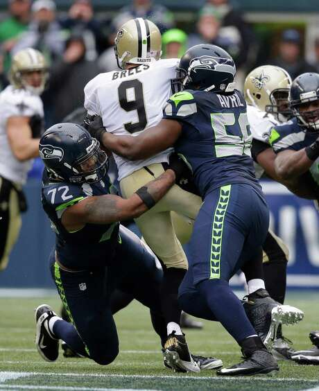 Seattle's Michael Bennett (72) and Cliff Avril (56) make a sandwich out of New Orleans' Drew Brees with their third-quarter sack Saturday. Photo: Elaine Thompson, STF / AP