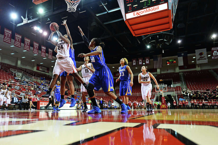 Lamar Lady Cardinals Alice Robinson, No. 24, left, drives the ball in during Saturday's game against McNeese State Cowgirls at the Montagne Center. Michael Rivera/@michaelrivera88   Photo taken Saturday, 01/11/14