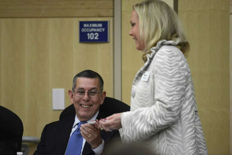 South San ISD's interim superintendent Abelardo Saavedra accepts business cards from Marian Strauss of Executive Search Services during a board meeting on Thursday, Jan. 9, 2014. Attorney Pablo Escamilla sits at left. Strauss and her group are tasked with conducting a nationwide search for a permanent superintendent for the district. Photo: San Antonio Express-News / San Antonio Express-News
