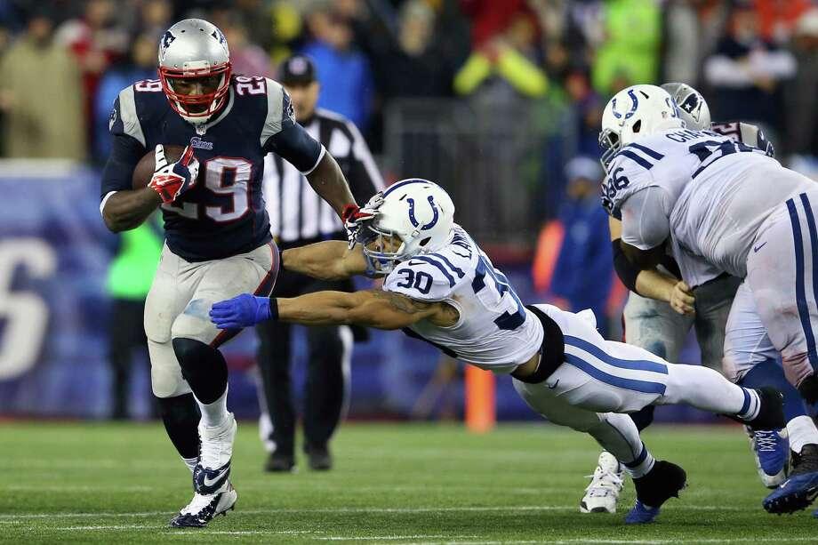 The Patriots' LeGarrette Blount, left, shoves aside the Colts' LaRon Landry en route to a 73-yard, fourth-quarter touchdown run. Photo: Al Bello, Staff / 2014 Getty Images