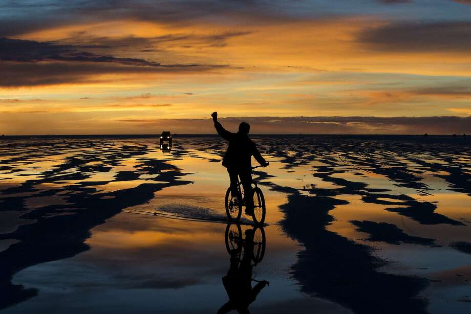A bicyclist waves to his friends' car on the Uyuni Salt Flats in Uyuni, Bolivia, where Stage 8 of the Dakar Rally was being held for motorcycles and quads. Photo: Victor R. Caivano, Associated Press