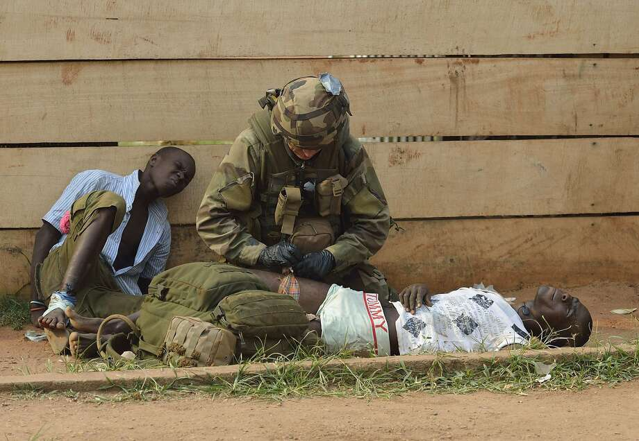 A French army medic gives first aid emergency medical care to two injured looters who were shot at as they were being chased away by people who they were looting from, on January 11, 2014, near the 'Reconciliation crossroad' in Bangui. A top UN official called for calm today in the Central African Republic, following the resignation of its president and prime minister after months of sectarian violence.    TOPSHOTS/AFP PHOTO/ERIC FEFERBERGERIC FEFERBERG/AFP/Getty Images Photo: Eric Feferberg, AFP/Getty Images