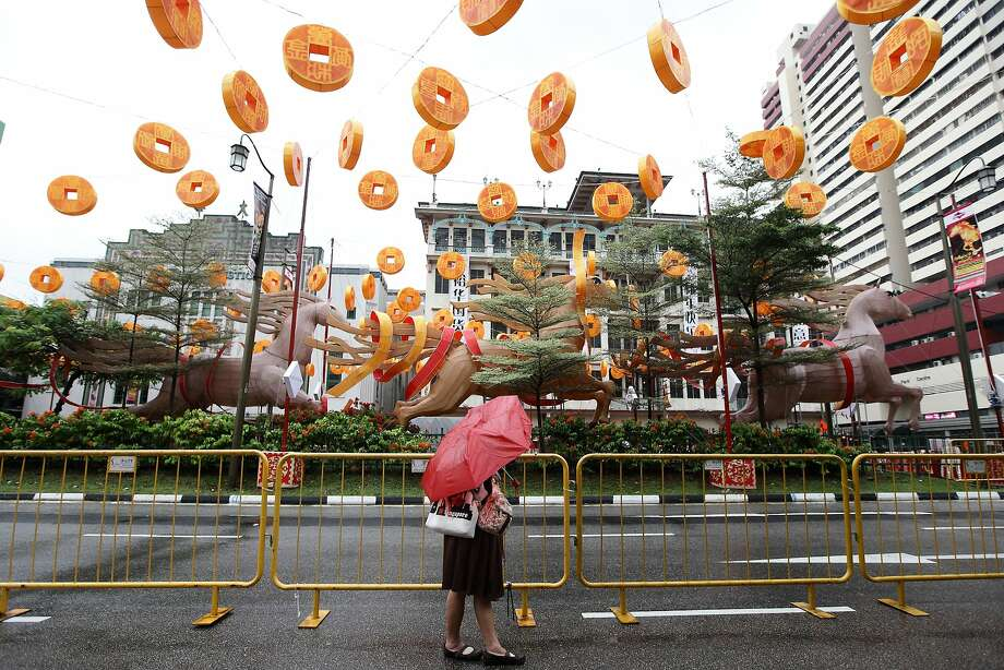 SINGAPORE - JANUARY 11:  A woman views the decoration on the street of Chinatown on January 11, 2014 in Singapore. On January 31st, people around the world will welcome the Year of the Horse, one of the most anticipated holidays of the Chinese calendar. Also known as the Spring festival or the Lunar New Year, the celebrations last for about 15 days.  (Photo by Suhaimi Abdullah/Getty Images) *** BESTPIX *** Photo: Suhaimi Abdullah, Getty Images