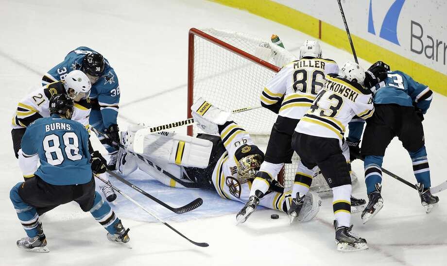 Boston goalie Tuukka Rask makes a diving save among a mass of skaters in the first period. He stopped 26 shots as he handed the Sharks only their second home regulation loss this season. Photo: Marcio Jose Sanchez, Associated Press