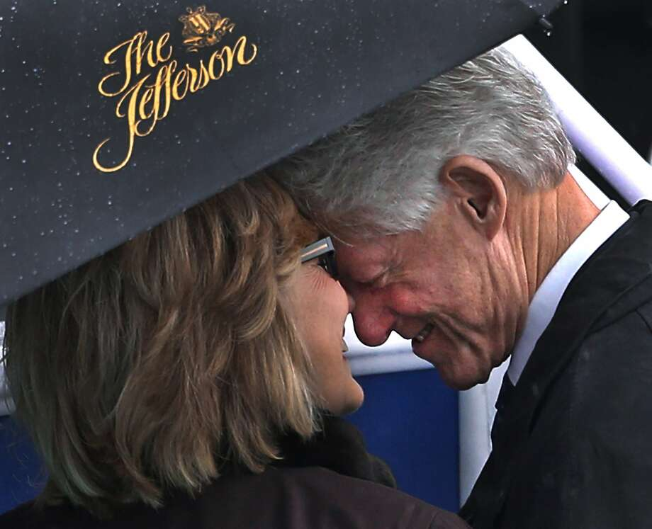 Former President Bill Clinton and his wife, former Secretary of State Hillary Rodham Clinton, share a moment under an umbrella before the rainy inauguration of democratic Virginia Gov. Terry McAuliffe in Richmond, Va., Jan. 11, 2014. Photo: P. Kevin Morley, Associated Press