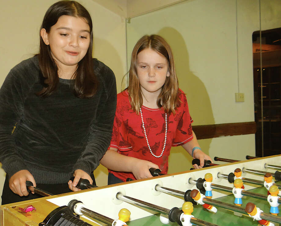 Filipa Ramos and Emily McNee play foosball Friday at the Westport Weston Family Y. Photo: Mike Lauterborn / Westport News contributed