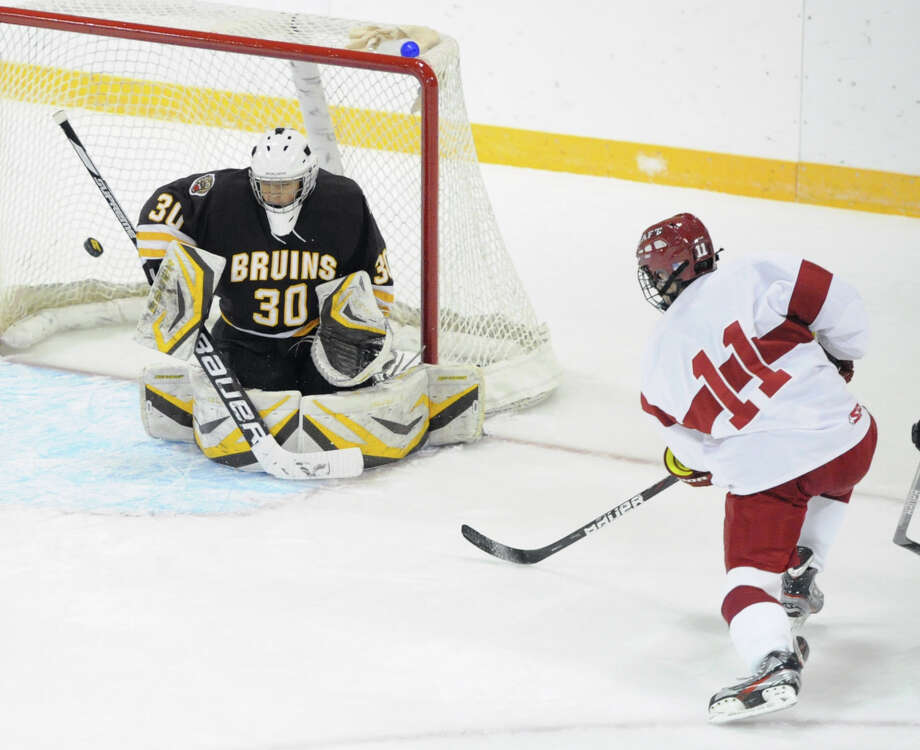 At left, Brunswick goalie Matteo Esposito (# 30) is unable to make the stop on a goal by Taft's Dan Quirk (# 11) during the first period of the boys high school ice hockey game between Brunswick School and Taft School at Brunswick in Greenwich, Wednesday afternoon, Nov. 20, 2013. Photo: Bob Luckey / Greenwich Time