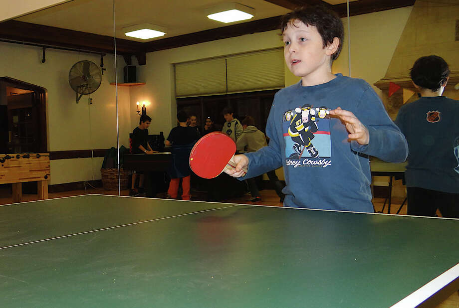 Josh Paul, 11, plays ping pong at the Westport Weston Family Y's Teen Night. Photo: Mike Lauterborn / Westport News contributed