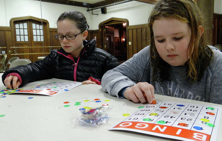 Eleven-year-olds Mia Daignault and Jane Van Arsdale enjoy a round of bingo Friday at Teen Night. Photo: Mike Lauterborn / Westport News contributed