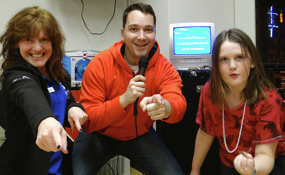 Danette Meigel, of Westport Weston Family Y's membership services; Jay Jaronko, senior program director, and Emily McNee, 11, in a spirited karaoke performance at the Y. Photo: Mike Lauterborn / Westport News contributed