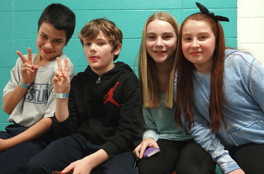 Adam Echevarria, 12; Alex Dowd, 11; Erica Fanning, 12, and Ella Bloomingdale, 11, relax poolside at the Westport Weston Family Y on Friday. Photo: Mike Lauterborn / Westport News contributed