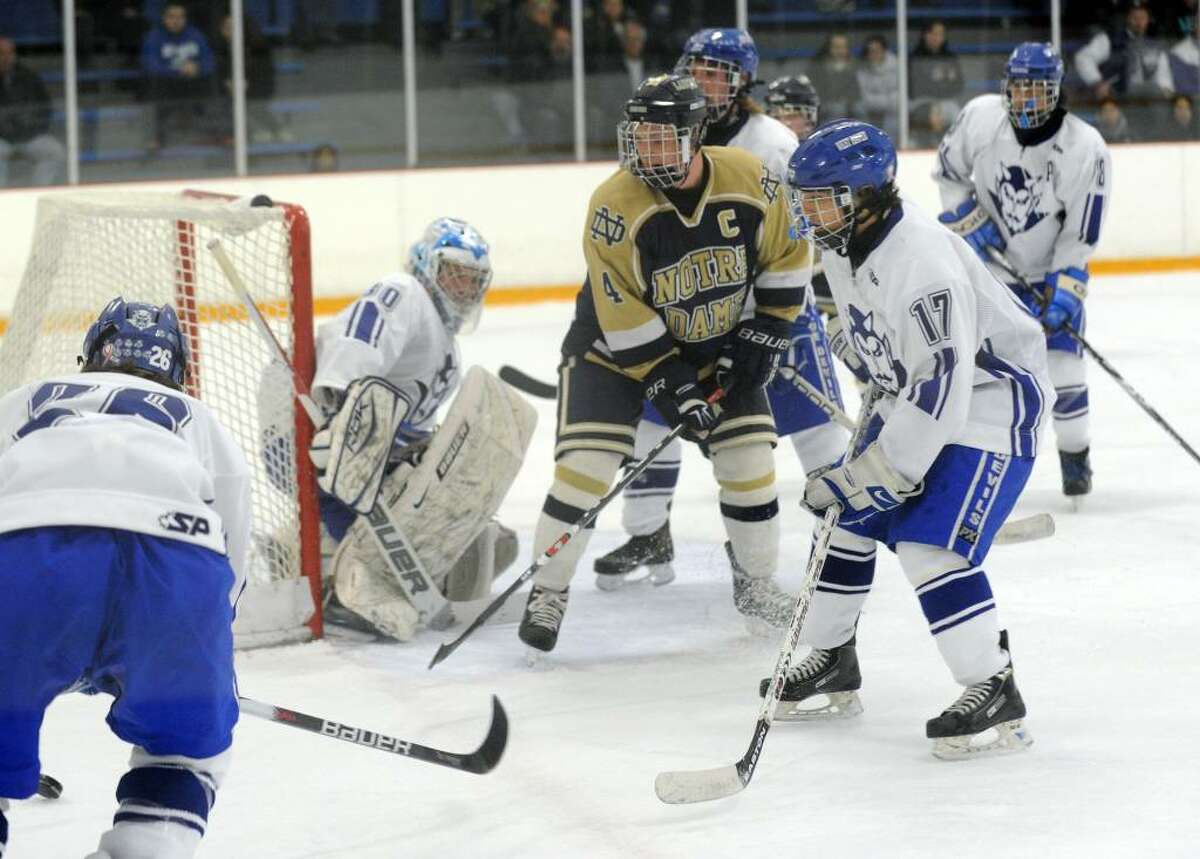 Notre Dame's Tyler Schmarr, in center, tracks the puck, during hockey action against West Haven in West Haven, Conn. on Wednesday Feb. 03, 2010.