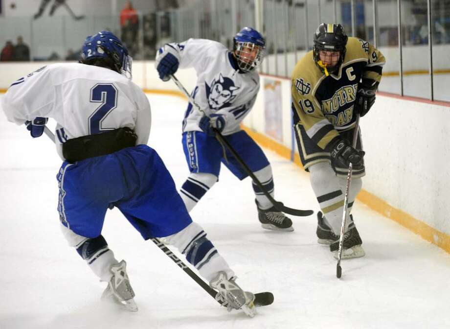 Notre Dame's Steve Hotchkiss, right, tries to intercept the puck from a West Haven player, during hockey action in West Haven, Conn. on Wednesday Feb. 03, 2010. Photo: Christian Abraham
